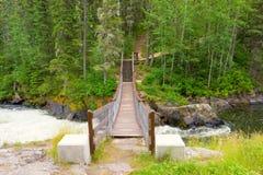 Un puente de balanceo sobre un río en un parque provincial en Canadá imagenes de archivo