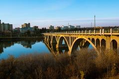 Un puente de oro que refleja en la superficie transparente del río en la puesta del sol imagen de archivo libre de regalías