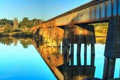 Un puente del carril cruza un río de movimiento lento foto de archivo