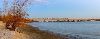 Un puente ferroviario largo sobre el río Visión desde la orilla en la puesta del sol Imagenes de archivo