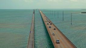 Un puente largo de la carretera que cruza el océano con el tráfico que mueve ambas direcciones almacen de video