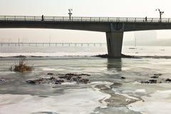Un puente sobre un río ice-covered Foto de archivo libre de regalías