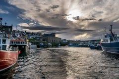 Un puerto con los barcos vistos del mar con las nubes de tormenta fotografía de archivo