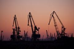 Un puerto en la puesta del sol, con tres grúas Fotos de archivo libres de regalías