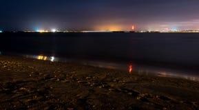 Un puerto y una playa en la noche con las luces y la estrella irradia foto de archivo