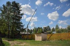 Un puits couvert - une grue, dans un village à distance dans la forêt Photo libre de droits