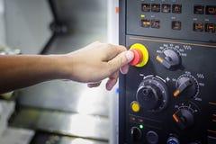 Un pulgar listo para presionar el botón de paro de emergencia en el panel de control de Fotografía de archivo libre de regalías