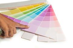 Un punto de la mano a las muestras coloreadas para elige la muestra de la pintura en el fondo blanco Imagen de archivo