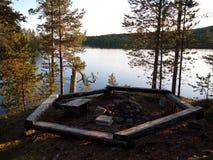 Un punto di campeggio finlandese del fuoco dal lago Immagine Stock