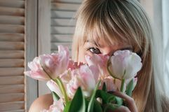 Un punto di vista del primo piano di una donna bionda con i fiori rosa fotografia stock