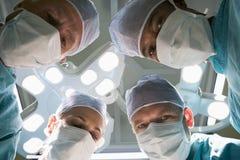 Un punto di vista di angolo basso di quattro chirurghi Fotografia Stock