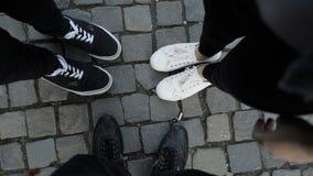 Un punto di vista di POV di tre piedi degli amici che camminano e che imbrogliano intorno stock footage