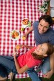 Un punto di vista elevato di due amici sorridenti come si trovano sui wi di una coperta Immagine Stock