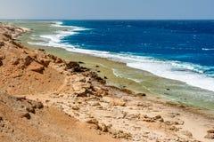 Un punto di vista lungo del deserto e di ampia Coral Reef con le grandi onde spumate ed i pilastri soli a Calimera Habiba Beach R immagine stock libera da diritti