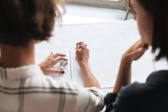 Un punto di vista posteriore di due donne che lavorano dalla tavola Fotografia Stock