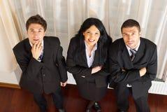 Un punto di vista superiore di tre genti di affari che osservano in su Immagine Stock Libera da Diritti
