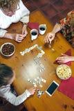 Un punto di vista superiore di tre generazioni femminili che giocano domino Fotografie Stock