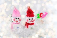 Un pupazzo di neve di due giocattoli con il fondo festivo di Natale Fotografia Stock