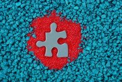 Un puzzle vert sur le sable rouge et les pierres bleues Image stock