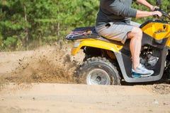 Un quadbike de ATV consigue pegado en un camino arenoso cerca de bosque y la rueda-vuelta el tener que hace un espray de la arena Fotos de archivo