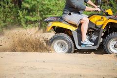Un quadbike de ATV consigue pegado en un camino arenoso cerca de bosque y la rueda-vuelta el tener que hace un espray de la arena Fotografía de archivo