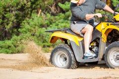 Un quadbike de ATV consigue pegado en un camino arenoso cerca bosque y de tener Fotografía de archivo