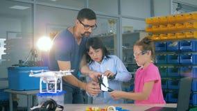 Un quadcopter está consiguiendo cambió por los niños y el técnico de laboratorio almacen de metraje de vídeo