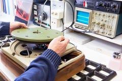 Un réparateur de haute fidélité mettant une pièce de disque dans une plaque tournante photos libres de droits
