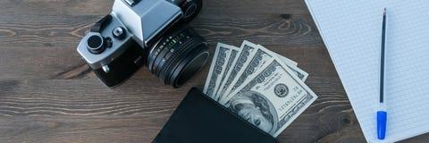 Un rétro appareil-photo, une bourse avec l'argent et un carnet avec un stylo sur une table en bois photo libre de droits