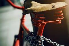 Un rétro vélo rouge est attaché avec une chaîne en métal à un poteau images libres de droits