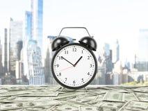 Un réveil est arrangé sur la surface qui est couverte par des notes du dollar Panorama de New York sur le fond Photographie stock libre de droits