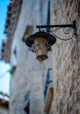 Un réverbère antique dans le village médiéval espagnol avec des maisons Photographie stock libre de droits