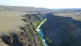 Un río azul corre a lo largo del barranco En los bancos del río crece la hierba verde y árboles fotografía de archivo libre de regalías