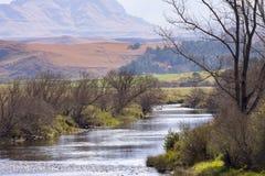 Un río corre a través de las colinas de la cordillera de Drakensberg en Underberg en Suráfrica Foto de archivo