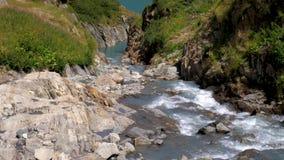 Un río del derretimiento del glaciar fluye sobre las rocas en un alto situado lago en los picos alpinos de Suiza metrajes