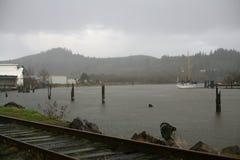 Un río en la lluvia con un barco Foto de archivo libre de regalías