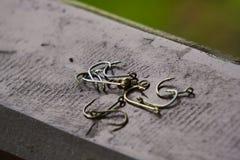 Un racimo de ganchos de pesca en un carril de mano de puente de madera del ` s de la charca fotos de archivo