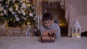 Un ragazzino apre una scatola con un regalo e si rallegra la menzogne sul pavimento vicino all'albero di Natale stock footage