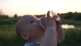 Un ragazzino beve una bevanda da un biberon nel campo al rallentatore stock footage