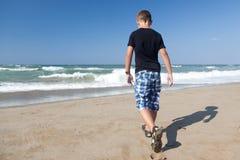 Un ragazzino che cammina da solo sulla spiaggia 1 Immagine Stock Libera da Diritti