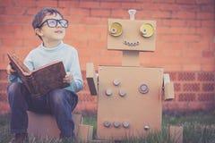 Un ragazzino che legge al robot dalle scatole di cartone all'aperto Immagine Stock Libera da Diritti