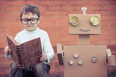 Un ragazzino che legge al robot dalle scatole di cartone all'aperto Immagini Stock