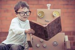 Un ragazzino che legge al robot dalle scatole di cartone all'aperto Immagine Stock