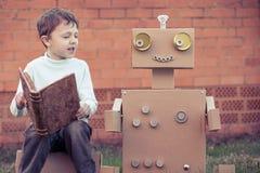 Un ragazzino che legge al robot dalle scatole di cartone all'aperto Immagini Stock Libere da Diritti