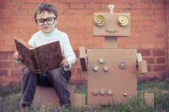 Un ragazzino che legge al robot dalle scatole di cartone all'aperto Fotografie Stock