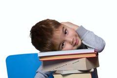 Un ragazzino che si siede ad una tabella con i libri Immagini Stock