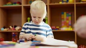 Un ragazzino che si siede alla tavola, tenendo gli indicatori e gli sguardi loro video d archivio