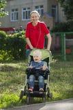 Un ragazzino che si siede in una sedia a rotelle e che cammina con sua madre Fotografia Stock