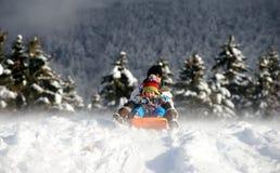 Un ragazzino che sledging nella neve Fotografia Stock