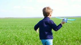 Un ragazzino che tiene un giocattolo spiana ed illustra il volo La macchina fotografica segue il bambino corrente Il bambino feli stock footage